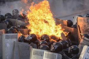 Interior Ministry members are on fire, caused by molotov cocktails hurled by anti-government protesters, as they stand guard during clashes in Kiev